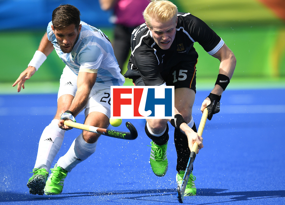 Argentina's Agustin Mazzilli (L) and Germany's Tom Grambusch chase the ball during the men's field hockey Argentina vs Germany match of the Rio 2016 Olympics Games at the Olympic Hockey Centre in Rio de Janeiro on August, 11 2016. / AFP / MANAN VATSYAYANA        (Photo credit should read MANAN VATSYAYANA/AFP/Getty Images)