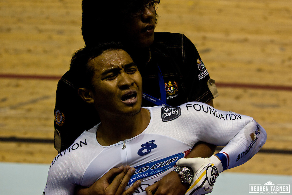 Azizulhasni Awang collapses into the arm's of a team official after finishing the Men's Keirin Final with a splinter through his leg. He took Bronze. <br /> <br /> A major crash on the final bend of the Men's Keirin, Final left a number of injuries. The worst appeared to be a splinter which penetrated right through the leg of the Malaysian rider Azizulhasni Awang. Awang managed to cross the line with the splinter in place, to claim the Bronze medal.