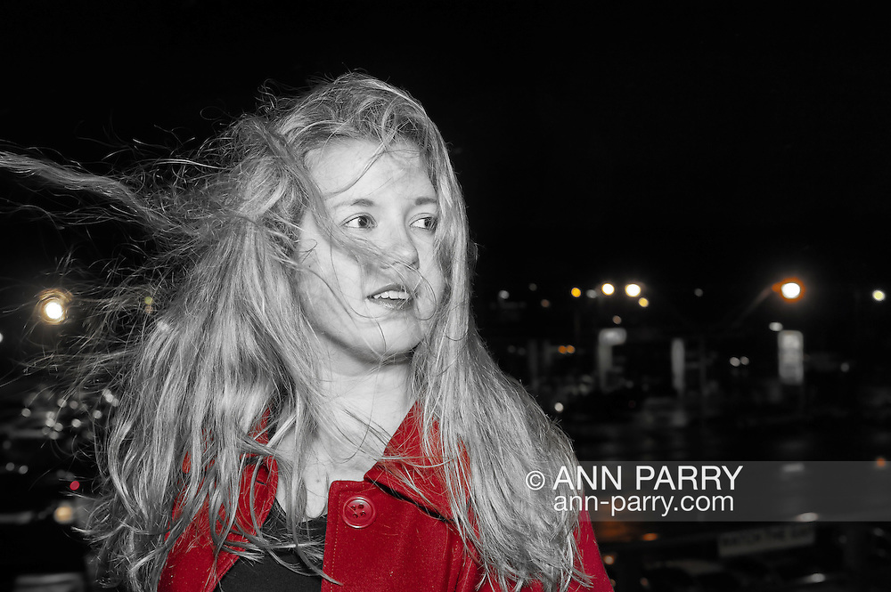 Teen girl in red coat outdoors on with long blonde hair blowing in windy rainy night on elevated train platform, USA.