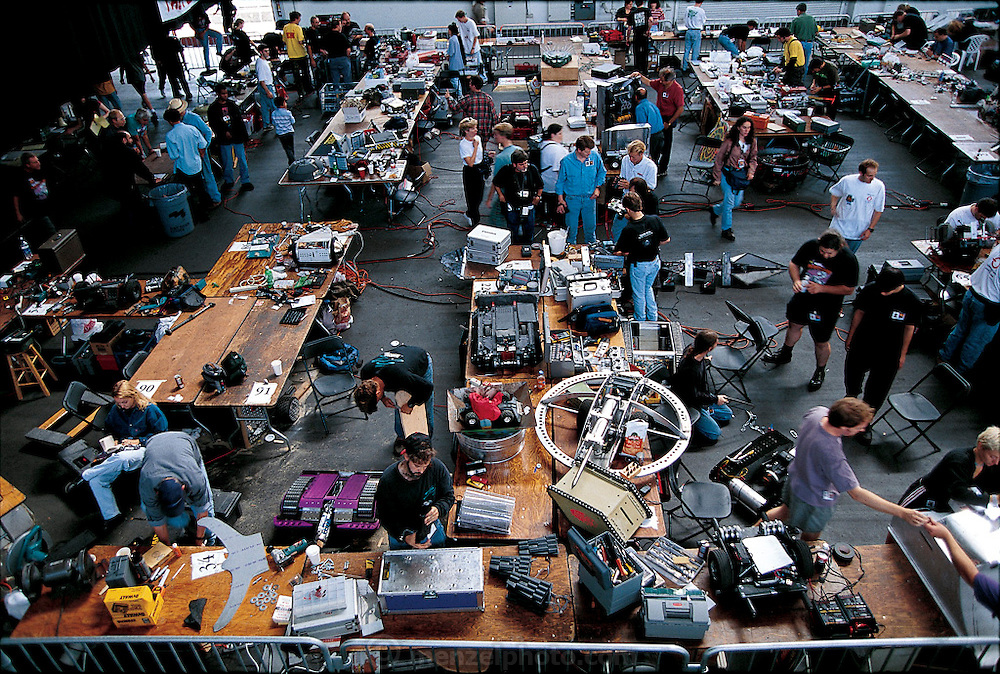 After the battle at San Francisco's Robot Wars, robot owners quickly repair what they can in the adjacent pit area . Full of machines being groomed for combat and surgically rescued after it, the pit is a sort of electronic fighter's dressing room and hospital emergency room. Video monitors above the pit give contestants a view of the action. At Robot Wars, a two-day festival of mechanical destruction at San Francisco's Fort Mason Center. California. From the book Robo sapiens: Evolution of a New Species, page 204 top.