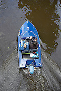 Twee mannen varen in een speedboot door de Oudegracht in Utrecht.<br />