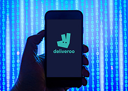 Person holding smart phone with Deliveroo  logo displayed on the screen. EDITORIAL USE ONLY