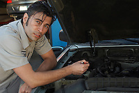 Mechanic pointing at engine, portrait