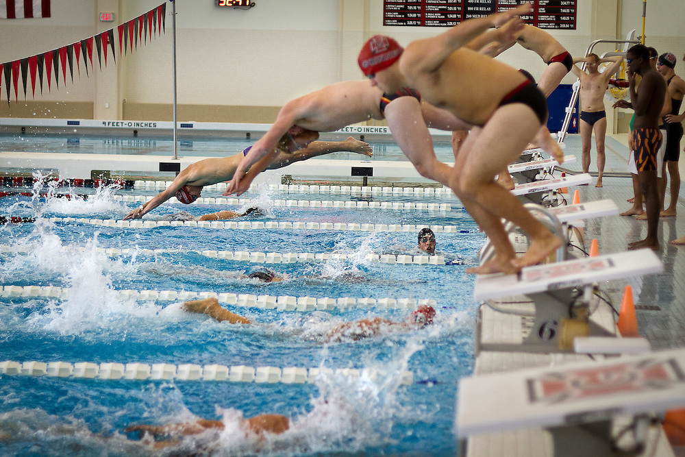 Grinnell College swimmers enter the water during the Men's 4x50m relay of the Alumni Meet held in the Russell K. Osgood Pool on Saturday.