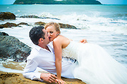 Bride on top of groom kissing while in the water at cairns