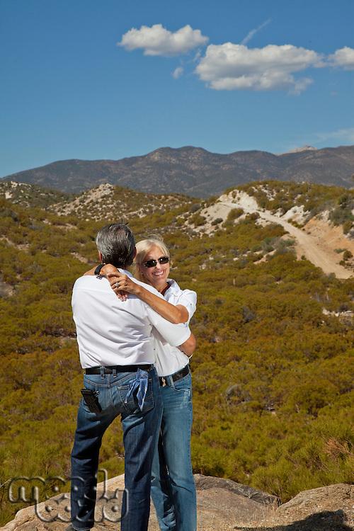 Senior couple hug with desert in background