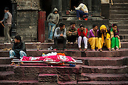 """4th May 2015, Kathmandu, Nepal. A Hindu family in mourning for their mother lying on a bier on the cremation ghats at the Pashupatinath Temple complex on the 4th May 2015, Kathmandu, Nepal. Their mother had an operation at a Kathmandu Hospital but when the earthquake struck the hospital ceased to function and as a result she died<br /> <br /> The Pashupatinath Temple is a famous, sacred Hindu temple dedicated to Pashupatinath is located on the banks of the Bagmati River 5 kilometres north-east of Kathmandu Valley in the eastern city of Kathmandu the capital of Nepal. This temple is considered one of the sacred temples of Hindu faith .The temple serves as the seat of the national deity, Lord Pashupatinath. This temple complex is on UNESCO World Heritage Sites's list Since 1979.This """"extensive Hindu temple precinct"""" is a """"sprawling collection of temples, ashrams, images and inscriptions raised over the centuries along the banks of the sacred Bagmati river"""" and is included as one of the seven monument groups in UNESCO's designation of Kathmandu Valley as a cultural heritage site. The temple is one of the 275 Paadal Petra Sthalams (Holy Abodes of Shiva) on the continent. Kotirudra Samhita, Chapter 11 on the Shivalingas of the North, in Shiva Purana mentions this Shivalinga as the bestower of all wishes. One of the major Festivals of the temple is Maha Shivaratri on which day over 700,000 devotees visit here.<br /> <br /> An earthquake with magnitude 7.8 occurred near Lamjung, Nepal, 50 miles northeast of the capital Kathmandu at 06:11:26 UTC on Apr 25, 2015. The capital has seen considerable devastation including the nine-story Dharahara Tower, one of Kathmandu's landmarks built by Nepal's royal rulers as a watchtower in the 1800s and a UNESCO-recognised historical monument. It was reduced to rubble and there were reports of people trapped. Portions of historic buildings in the World Heritage gazetted site of Patan have also been destroyed as well as many buildings in t"""