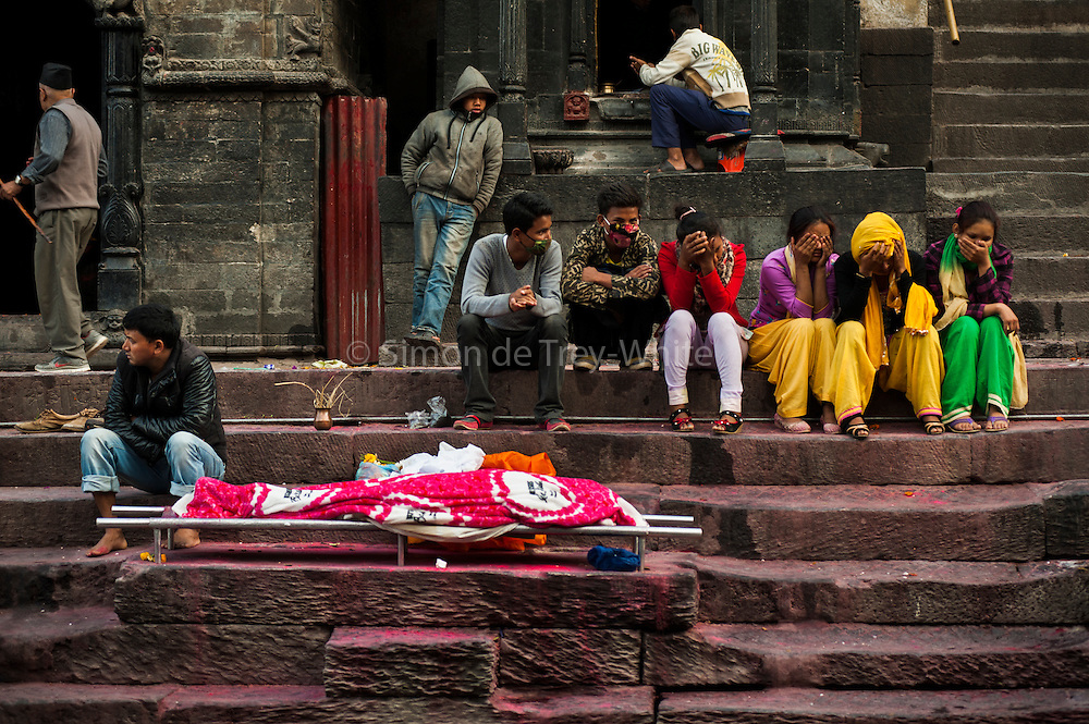 4th May 2015, Kathmandu, Nepal. A Hindu family in mourning for their mother lying on a bier on the cremation ghats at the Pashupatinath Temple complex on the 4th May 2015, Kathmandu, Nepal. Their mother had an operation at a Kathmandu Hospital but when the earthquake struck the hospital ceased to function and as a result she died<br /> <br /> The Pashupatinath Temple is a famous, sacred Hindu temple dedicated to Pashupatinath is located on the banks of the Bagmati River 5 kilometres north-east of Kathmandu Valley in the eastern city of Kathmandu the capital of Nepal. This temple is considered one of the sacred temples of Hindu faith .The temple serves as the seat of the national deity, Lord Pashupatinath. This temple complex is on UNESCO World Heritage Sites's list Since 1979.This &quot;extensive Hindu temple precinct&quot; is a &quot;sprawling collection of temples, ashrams, images and inscriptions raised over the centuries along the banks of the sacred Bagmati river&quot; and is included as one of the seven monument groups in UNESCO's designation of Kathmandu Valley as a cultural heritage site. The temple is one of the 275 Paadal Petra Sthalams (Holy Abodes of Shiva) on the continent. Kotirudra Samhita, Chapter 11 on the Shivalingas of the North, in Shiva Purana mentions this Shivalinga as the bestower of all wishes. One of the major Festivals of the temple is Maha Shivaratri on which day over 700,000 devotees visit here.<br /> <br /> An earthquake with magnitude 7.8 occurred near Lamjung, Nepal, 50 miles northeast of the capital Kathmandu at 06:11:26 UTC on Apr 25, 2015. The capital has seen considerable devastation including the nine-story Dharahara Tower, one of Kathmandu's landmarks built by Nepal's royal rulers as a watchtower in the 1800s and a UNESCO-recognised historical monument. It was reduced to rubble and there were reports of people trapped. Portions of historic buildings in the World Heritage gazetted site of Patan have also been destroyed as well as many buildings in the old city. <br /> <br /> PHOTOGRAP
