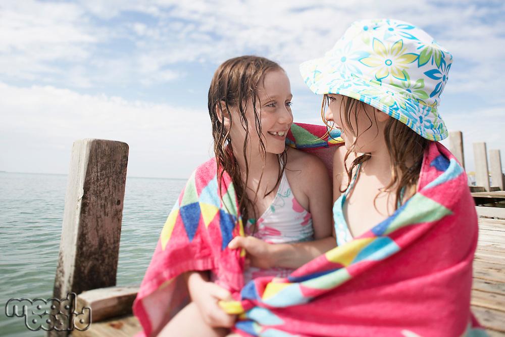 Two girls wrapped in towel sitting together at end of pier