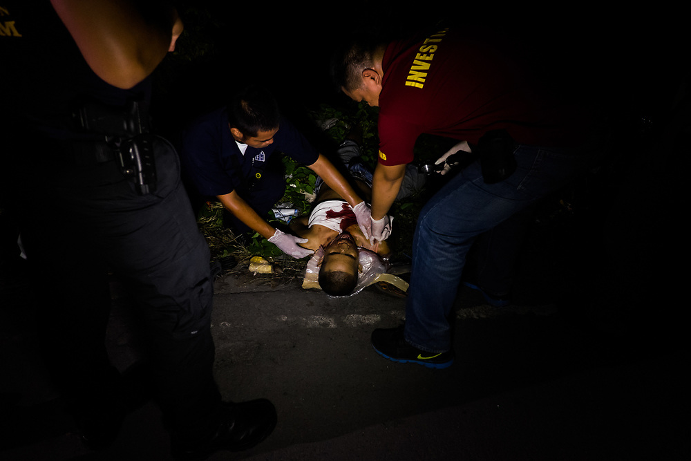 Police agents unfold the face of a victim wrapped in the tape.