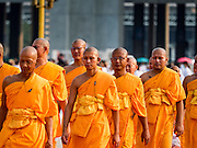 "22 FEBRUARY 2016 - KHLONG LUANG, PATHUM THANI, THAILAND:  Monks and novices file into the chedi before the evening service for Makha Bucha Day at Wat Phra Dhammakaya.  Makha Bucha Day is a public holiday in Cambodia, Laos, Myanmar and Thailand. Many people go to the temple to perform merit-making activities on Makha Bucha Day, which marks four important events in Buddhism: 1,250 disciples came to see the Buddha without being summoned, all of them were Arhantas, Enlightened Ones, and all were ordained by the Buddha himself. The Buddha gave those Arhantas the principles of Buddhism, called ""The ovadhapatimokha"". Those principles are:  1) To cease from all evil, 2) To do what is good, 3) To cleanse one's mind. The Buddha delivered an important sermon on that day which laid down the principles of the Buddhist teachings. In Thailand, this teaching has been dubbed the ""Heart of Buddhism."" Wat Phra Dhammakaya is the center of the Dhammakaya Movement, a Buddhist sect founded in the 1970s and led by Phra Dhammachayo.     PHOTO BY JACK KURTZ"