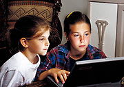 Young girls using a portable computer.