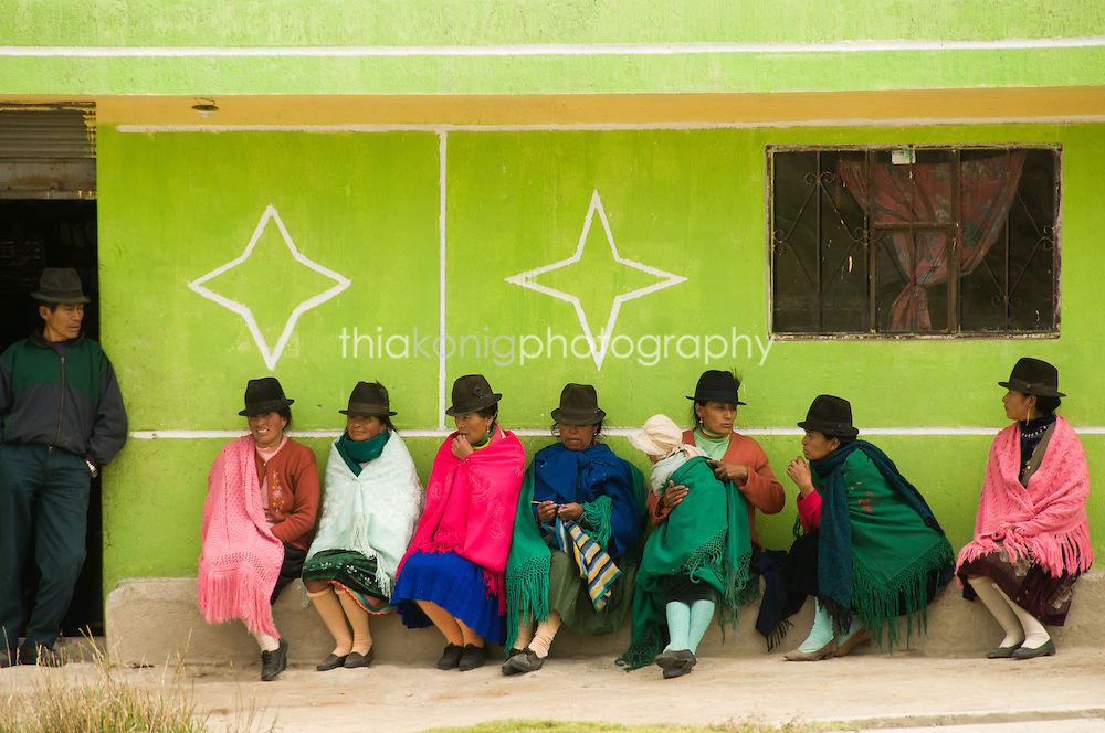 Group of locals sit outside green building, all wearing traditional hats, Andes Mountains, Ecuador.