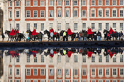 © Licensed to London News Pictures. 17/12/2018. London, UK. Members of the Household Cavalry Life Guards make their way across Horse Guards Parade reflected in a puddle and silhouetted against a sunlit Admiralty building . Photo credit: Peter Macdiarmid/LNP