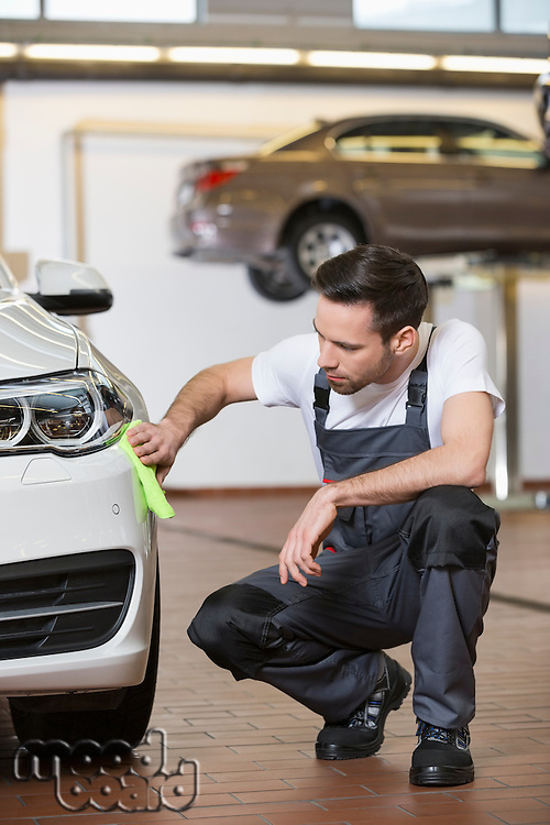 Full length of automobile mechanic cleaning car in workshop