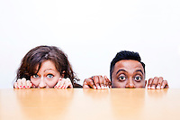 Work colleagues peeking over edge of table