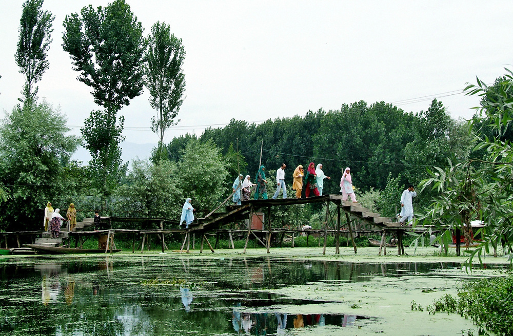 A group of people in colorful dress is crossing a bridge over one of the many canals in Srinagar, also called &quot;the Venice of the East&quot;.<br /> Photo by Lorenz Berna