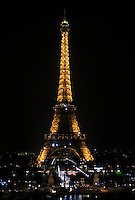 The Eiffel Tower lights up the night sky in Paris, France.