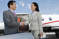 Mid-adult businesswoman and mid-adult businessman shaking hands in front of private plane.