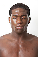Shirtless young African American man sweating over white background