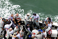 BOSS OF ALINGHI ERNESTO BERTARELLI WITH BOTTLE OF CHAMPAGNE IN HAND CONGRATULATES SKIPPER RUSSELL COUTTS AFTER CROSSING THE FINISH LINE TO WIN THE AMERICA'S CUP.  REST OF THE TEAM CELEBRATES.