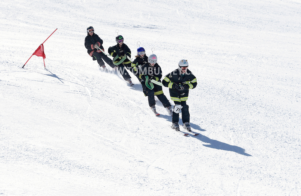 Bridgeville, New York - A team of young skiers wearing firefighter's coats heads down a course while carrying a fire hose at Holiday Mountain during the firemen's races on March 6, 2010.