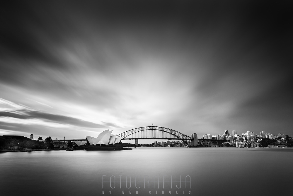 Iconic landmarks are iconic for a reason.<br /> Millions of photos have been taken of Sydney's famous Opera House and Harbour Bridge, and there will be millions more.<br /> The presence of these structures is amplified by the landscape that surrounds them, creating a whole which is greater than the sum of its parts.<br /> The sea below; the sky above.  White sails taking flight against a backdrop of the bridge stretching wide, anchoring both sides of the harbour.<br /> This eighty second exposure encompasses the natural world that frames these icons and from which they are inseparable.