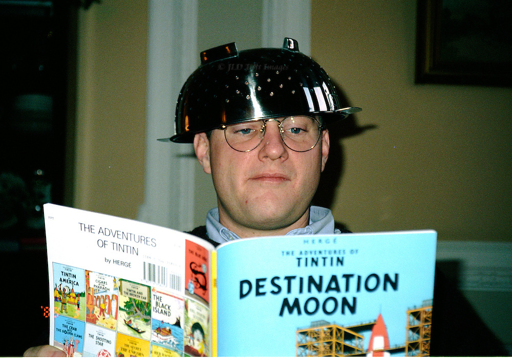 Young man with a sense of humor wears a kitchen strainer as a helmet while reading TinTin story about outer space.