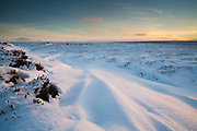 Last light of the day catches the gentle lines in the drifted snow on Burbage Moor, Peak District. A winter scene captured in December 2014.