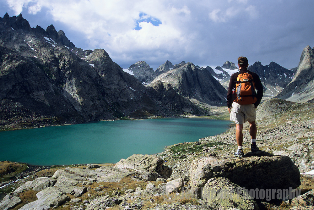A hiker surveys the view of Titcomb Basin in the Wind River Mountains, Wyoming.