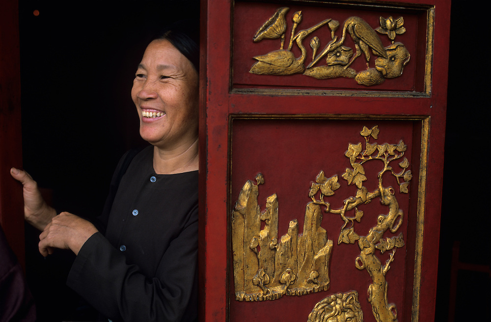 Asia, Vietnam, Woman stands by doorway inside Buddhist temple near Perfume Pagoda (Chua Huong)