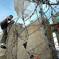 A Palestinian man climbs the separation wall in Abu Dis on Sunday May 14. 2006 in Abu Dis...Photo by Olivier Fitoussi