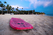 A boogie board in the sand on Waikiki Beach at dusk.