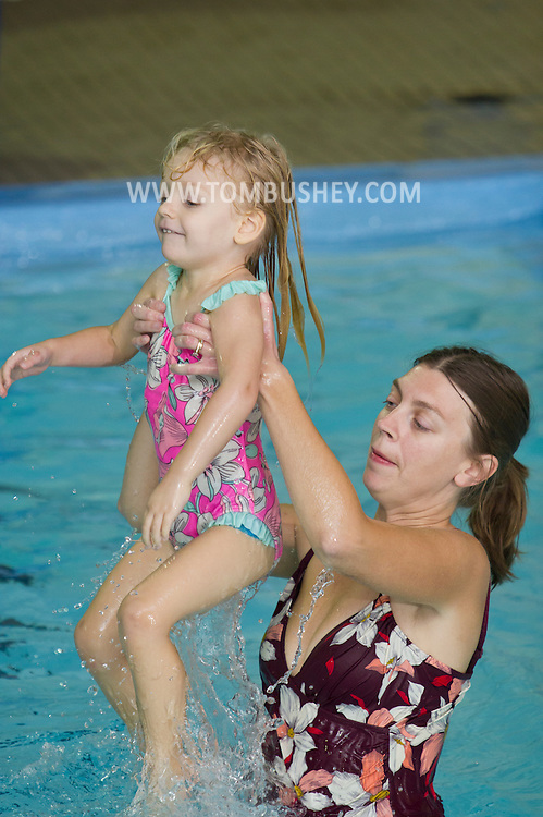Middletown, New York - A woman lifts her daughter out of the water during a parent and child swimming class at the YMCA of Middletown on Nov. 5, 2014.