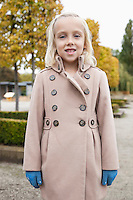 Portrait of cute little girl in winter coat standing at park