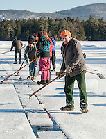Norman Lyford guides the ice slabs up the channel for loading during the Rockywold Deephaven Camp Ice Harvest on Tuesday afternoon.  Mr. Lyford has been working the annual ice harvest for 70 years.  (Karen Bobotas/for the Laconia Daily Sun)