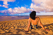 Woman sitting on Tunnels Beach at sunset, North Shore, Island of Kauai, Hawaii USA