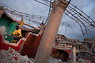 Govenrment-paid workers take apart an earthquake-damaged house in the Fort National neighborhood of Port-au-Prince, Haiti, Tuesday, March 30, 2010.  Many Haitians are working in a UN-sponsored program known as Cash-for-Work in which they make about $4 a day to clear rubble.