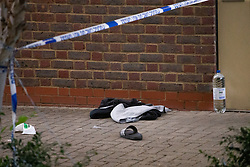 © Licensed to London News Pictures. 03/08/2020. London, UK. Discarded clothes and a bottle of water at the scene as police officers, forensics examiners and detectives work at the scene of a shooting at Tilson Gardens, that happened around 6.38pm on August 3rd in Brixton, where a man was taken to hospital with a gunshot injury. Photo credit: Paul Davey/LNP