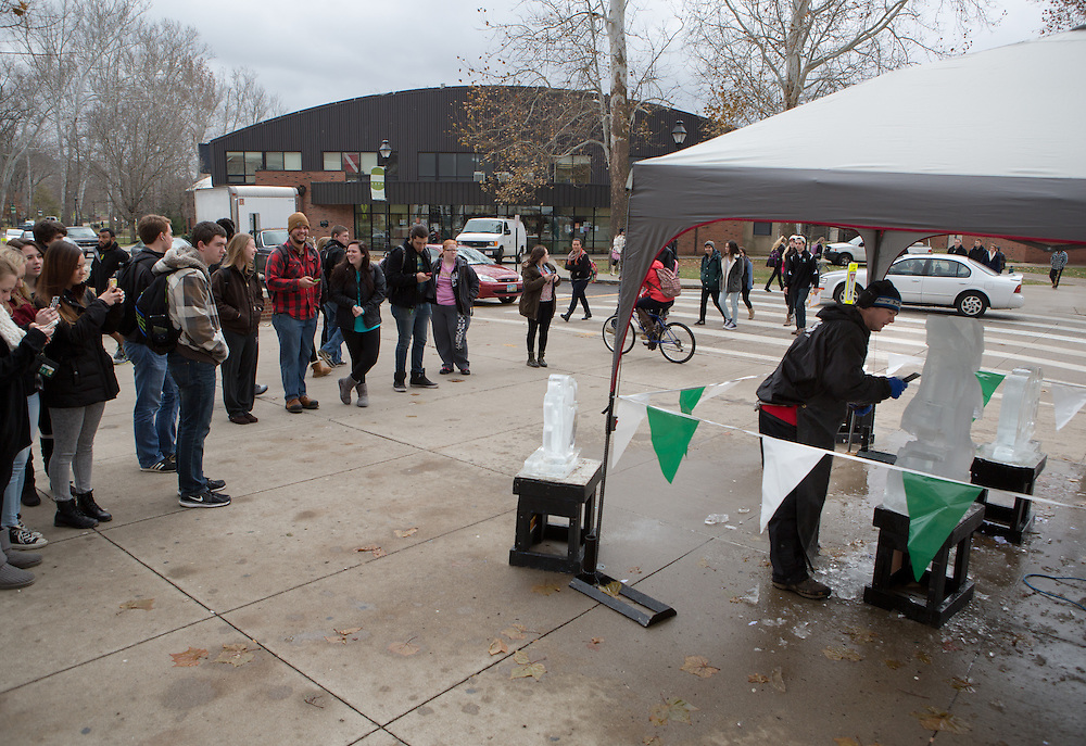 Students look on as ice carver Jeff Petercsak, of Rock on Ice, carves a penguin in front of Baker University Center on Dec. 3, 2014. Photo by Lauren Pond