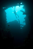 A diver with a video camera above the wreck of the 'Shinwa Maru', Manokwari, West Papua, Indonesia.