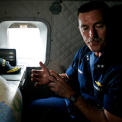 U.S. Coast Guard Rear Admiral Paul Zunkunft the Federal On Scene Coordinator for the gulf oil spill reviews a map of the source site during a flight on a C-144 U.S. Coast Guard Aircraft that flew over the source of the BP Plc Deep Water Horizon oil spill site in the Gulf of Mexico off the coast of Louisiana, U.S., on Sunday, July 11, 2010. Oil is once again gushing freely into the Gulf of Mexico as BP Plc is in the process of changing out the cap from the leaking well and plans to have a new cap installed over the next few days that will allow for oil to be captured efficiently. Photographer: Derick E. Hingle/Bloomberg