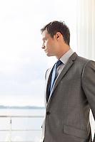 Pensive businessman standing by glass door in hotel
