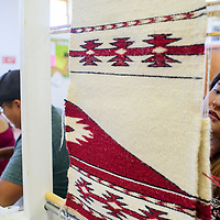 Kaylene Kinsel weaves a rug to make a rug dress Thursday at the Bread Springs Chapter House.