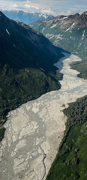The Tsirku River is a braided river near Haines, Alaska that eventually flows into the Chilkat River. At that intersection of the two rivers, the Tsirku River spreads out into a huge alluvial fan river delta. That area, is the primary area where bald eagles gather on the Chilkat River in the Alaska Chilkat Bald Eagle Preserve. This downriver view of the Tsirku River is several miles before the river leaves the steep walls of the river valley and forms the alluvial fan river delta.<br /> <br /> Bald eagles come to the alluvial delta area at the confluence of the Tsirku and Chilkat Rivers because of the availability of spawned-out salmon and open waters in late fall and early winter. The open water is due to a deep accumulation of gravel and sand that acts as a large water reservoir whose water temperature remains 10 to 20 degrees warmer than the surrounding water temperature. This warmer water seeps into the Chilkat River, keeping a five mile stretch of the river from freezing.