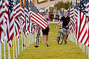"10 SEPTEMBER 2011 - TEMPE, AZ:    JULIANNE ANDERSON, left, and MATTHEW BOWLES, both from Tempe, AZ, walk through the ""Healing Field"" in Tempe, Saturday. The ""Healing Field,"" a display of 2,996 flags, one for each person killed in the September 11 terrorists attacks on the World Trade Center in New York City and Washington DC, have become an annual tradition in Tempe. The event is sponsored by the National Exchange Club.      PHOTO BY JACK KURTZ"