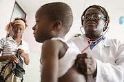 Dr. Denise Mobio examines Junior Karampire, 5, who suffers from recurring ear infections, while his mother Kadidiatou Sy, 27, waits at the Koumassi General Hospital in Abidjan, Cote d'Ivoire on Friday July 19, 2013.
