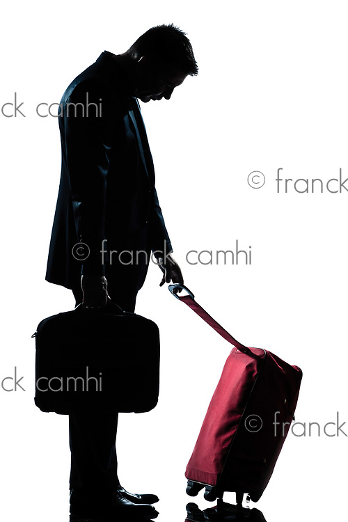 profile one caucasian business traveler man tired with suitcase  full length silhouette in studio isolated white background