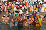 Indian Hindu pilgrims bathing in The Ganges River at Dashashwamedh Ghat in Holy City of Varanasi, Benares, India
