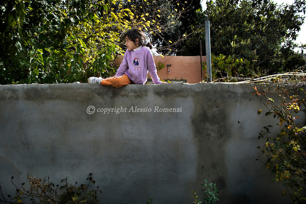 A palestinian girl sit on the separation wall between her house and the occupied house of the Palestinian Kurd family east Jerusalem's Sheikh Jarrah neighbourhood on December 4, 2009. Israeli settlers took over the house last month and hurled the Palestinian family's belongings into the street, armed with a court order secured after a protracted legal battle with the Palestinian family. In a confidential report dated on December 3, the European Union accused Israel of actively pursuing the annexation of Arab east Jerusalem and undermining hopes for peace with Palestinians.  .© ALESSIO ROMENZI